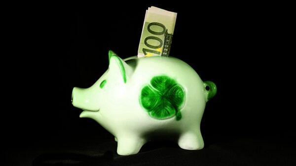 In einem weißen Sparschwein mit einem Kleeblatt befinden sich 100 Euro im Einwurf-Schlitz.
